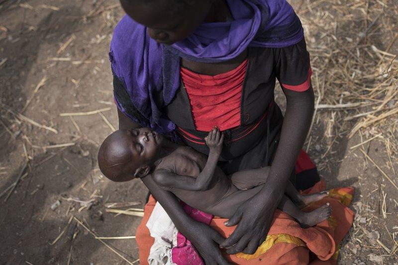 20歲的愛黛兒(Adel Bol)帶著自己年僅10個月的寶貝女兒,來到聯合國的物資發放處準備領取食物。(美聯社)