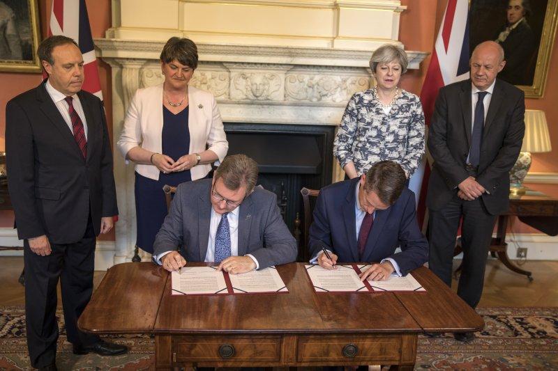DUP議員唐納森(Jeffrey Donaldson,左坐者)與英國保守黨黨鞭威廉森(Gavin Williamson,右坐者)簽訂協議,梅伊(右二)與佛斯特(左二)站在後方觀看(AP)