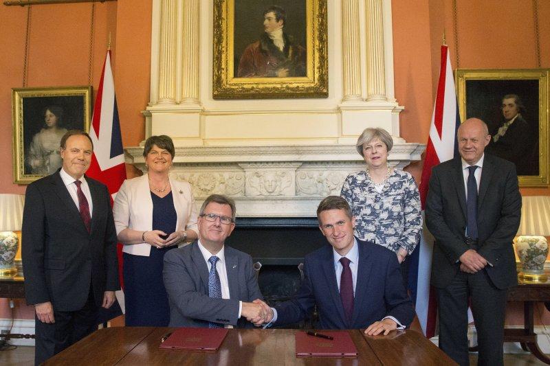 雙方簽訂協議後,DUP議員唐納森(Jeffrey Donaldson,左坐者)與英國保守黨黨鞭威廉森(Gavin Williamson,右坐者)握手(AP)