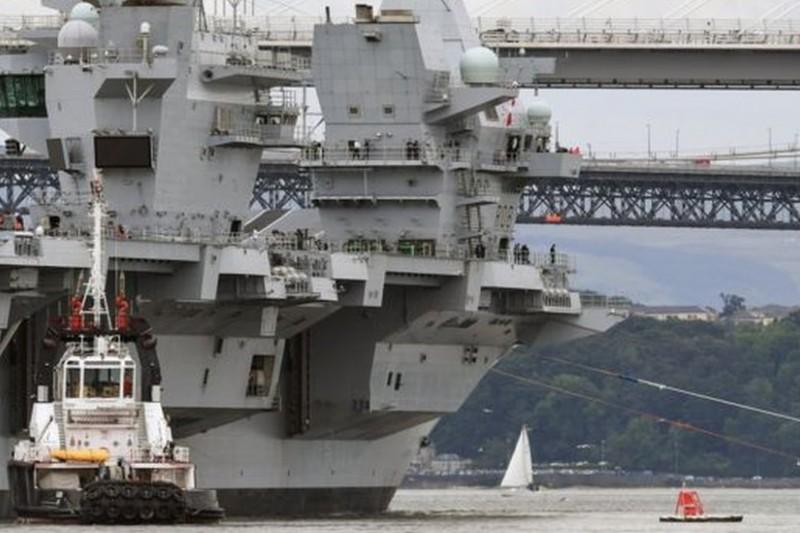 全新的英國皇家海軍「伊莉莎白女王號」航空母艦借著低潮下水,並通過沿途的大鐵橋。(BBC中文網)