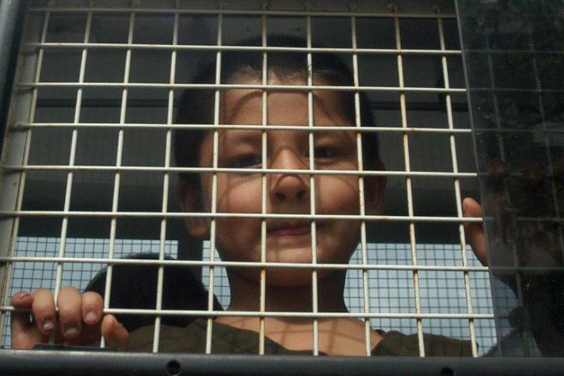 在泰國南部宋卡府一輛警車上的一名維吾爾族穆斯林男孩。(美國之音)
