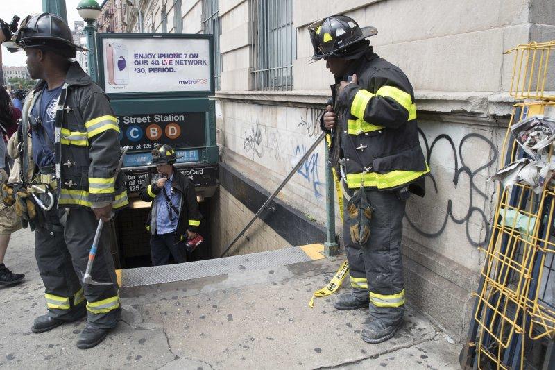 紐約地鐵出軌,消防人員趕到現場待命。(美聯社)