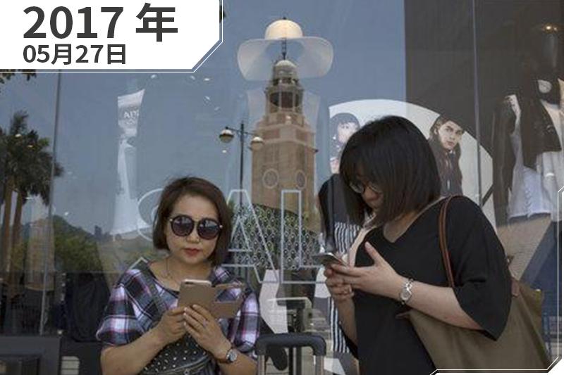 香港,2名女遊客在購物中心外面滑手機(照片:AP/製圖:風傳媒)