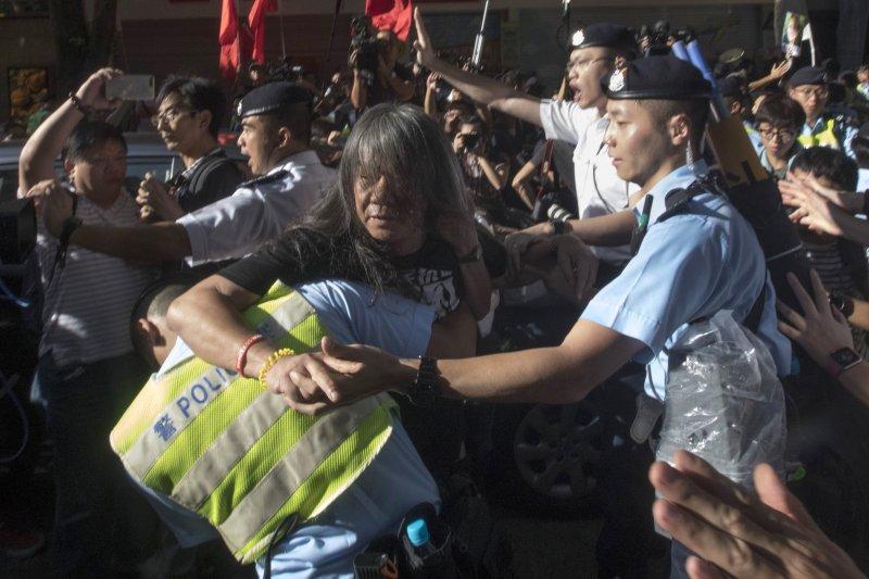 香港立法會議員「長毛」梁國雄被警方帶走。(美聯社)