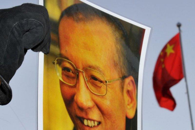 一位抗議者在中國駐奧斯陸大使館門外舉著劉曉波的照片。(美國之音)
