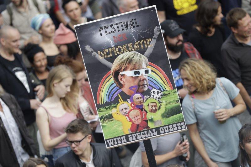 德國漢堡即將舉行G20峰會,一名反G20的示威民眾舉著嘲諷德國總理梅克爾的牌子,上面標語寫著:「民主節慶:梅克爾與她的特別客人。」