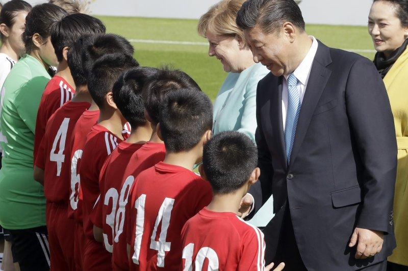 德國總理梅克爾和中國國家主席習近平,與中德青年足球隊員握手。(AP)