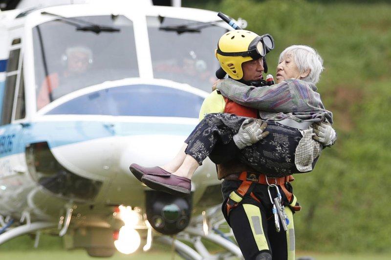 日本九州地區豪雨成災,一名消防人員抱起一位年邁災民準備撤離災區(AP)