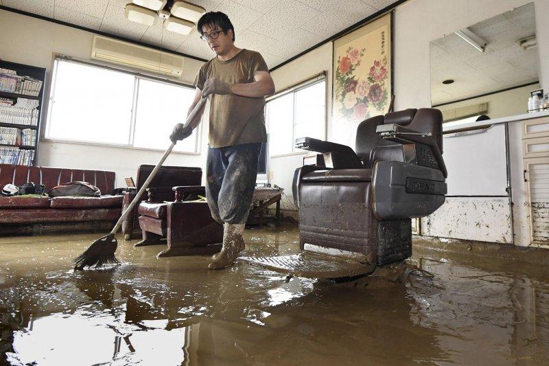 日本九州地區豪雨成災,許多民宅泡在水中,一位災民正在清理屋內的泥濘(AP)