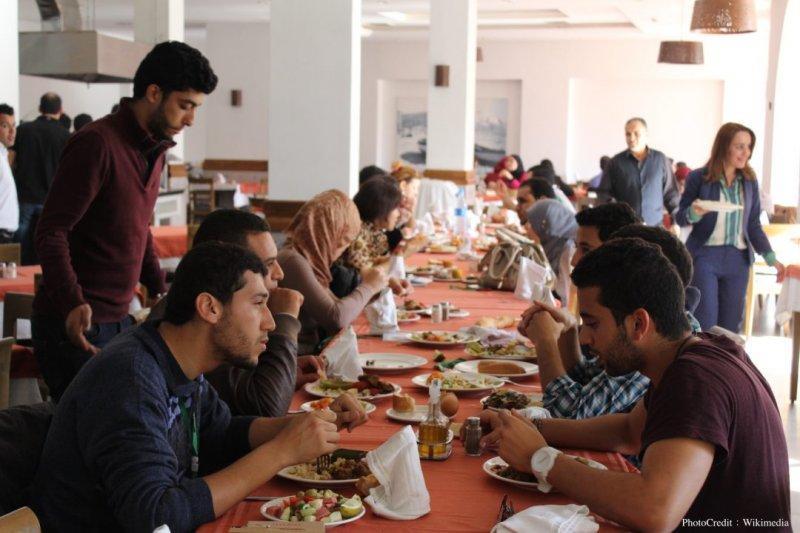 在電子商品造成人心遙遠的時代,共享餐桌的概念反而流行了起來。(圖/Wikimedia)