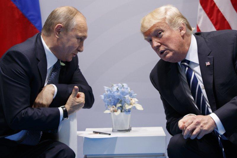 美國總統川普(右)與俄羅斯總統普京7日首度會面,川普側身專心聽著普京說話(AP)