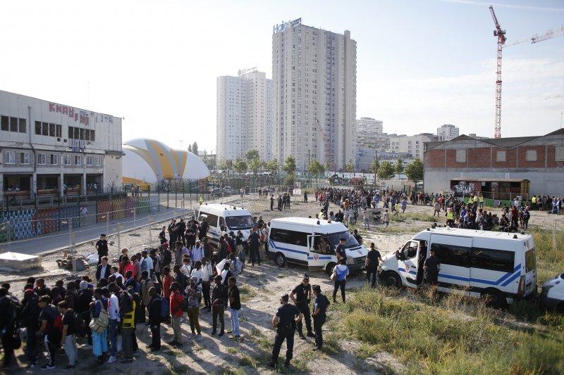 巴黎7日遷移上千位街頭的難民,被迫離開棲身之地的人們排隊準備搭乘巴士。(美聯社)
