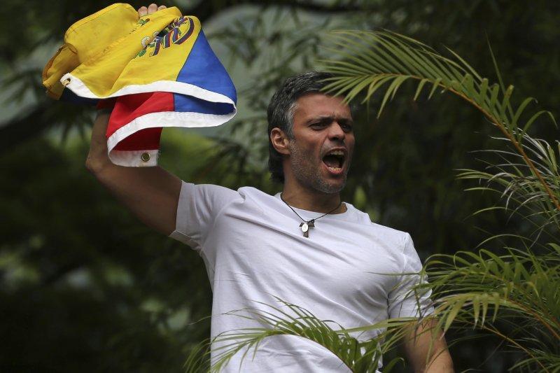 委內瑞拉反對黨「人民志願黨」領袖羅培茲在自家屋頂向支持者揮舞國旗(AP)