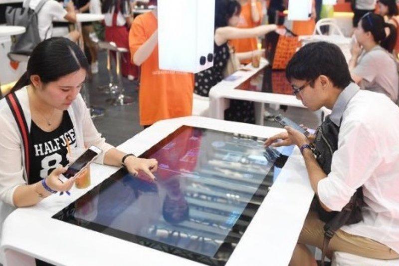 7月8日,杭州國際博覽中心舉辦的2017淘寶造物節上,顧客在「無人商店」內使用裝有觸控式螢幕的桌子體驗「虛擬購物」。(新華社)