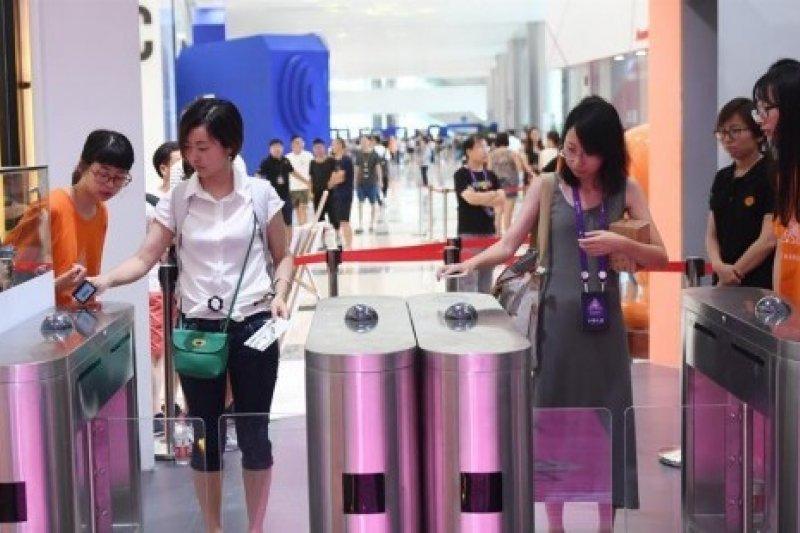7月8日,杭州國際博覽中心舉辦的2017淘寶造物節上,顧客使用手機掃碼進入「無人商店」內體驗。(新華社)