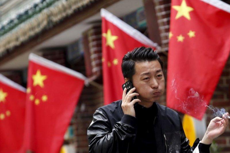 北京一名男子拿著香菸走過一家餐廳。(美國之音)