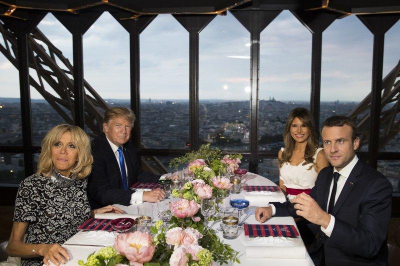 13日晚間,法國總統馬克宏(右一)與夫人布莉姬特(左一)在巴黎艾菲爾鐵塔的「朱爾斯凡爾納」米其林餐廳設宴款待美國總統川普(左二)(AP)