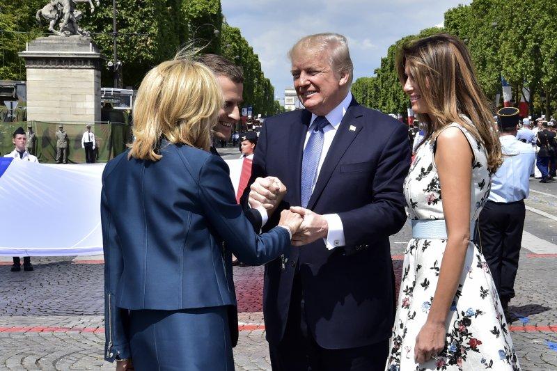 美國總統川普(右二)在法國國慶閱兵式結束後,熱情緊握法國總統夫婦的手(AP)