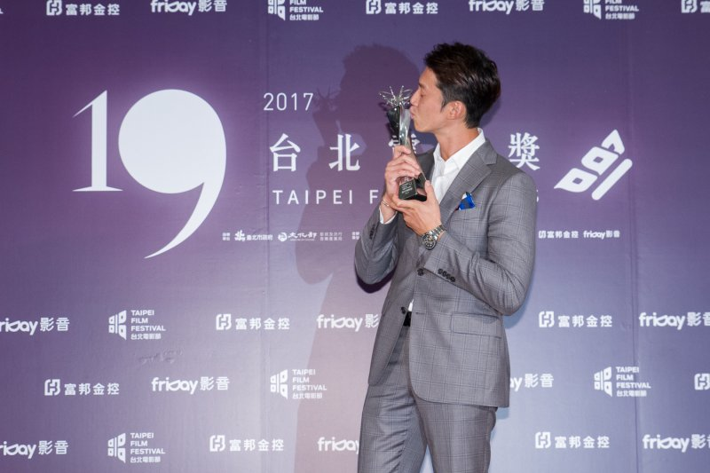 吳慷仁以《白蟻-慾望謎網》拿下台北電影獎最佳男主角獎,開心的親吻獎座。(圖/台北電影節提供)
