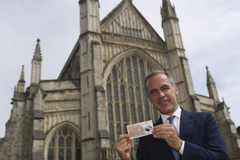 英格蘭銀行行長卡尼(Mark Carney)在溫徹斯特大教堂前展示印著珍.奧斯汀肖像的10英鎊新鈔(AP)
