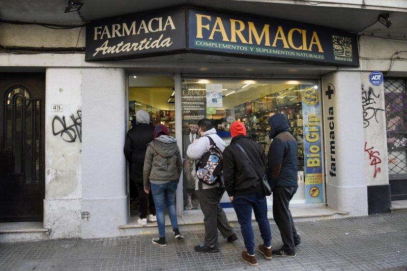 19日起,烏拉圭公民及永久居民可先向政府註冊,然後至藥局購買大麻,大批民眾群聚藥局外。(美聯社)