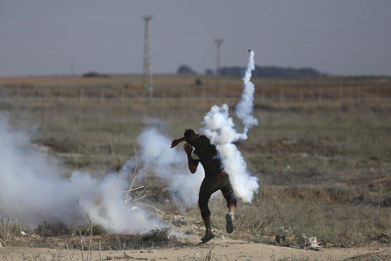一位巴勒斯坦的抗議者在加薩走廊將以色列發射的催淚彈丟回以方。(美聯社)