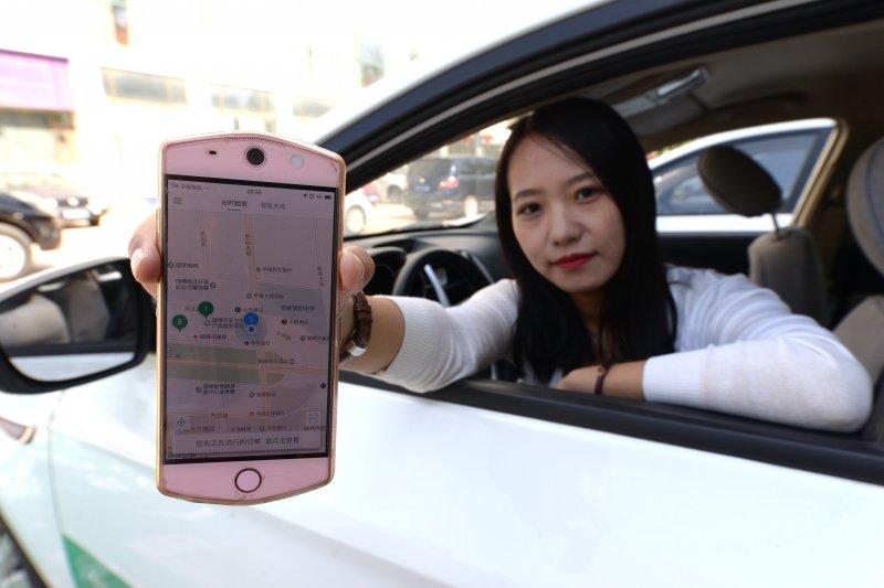 中國共用經濟能走多遠?邯鄲(河北)市民在演示使用手機軟體定位「共用汽車」(新華社)