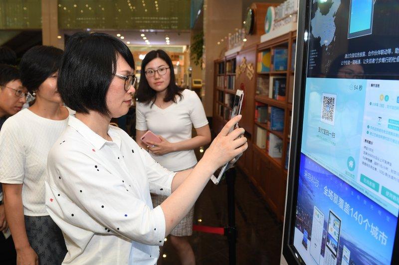 中國共用經濟能走多遠?城市管理者在杭州圖書館體驗信用自助借還共用充電寶(新華社)