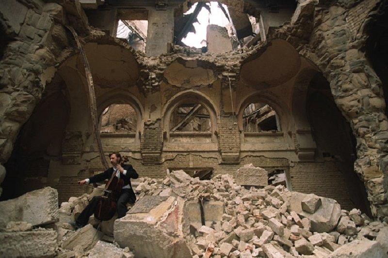 斯梅洛維奇在國家圖書館的廢墟中演奏。俄羅斯攝影師Mikhail Evstafiev於1992年拍攝。(維基百科)