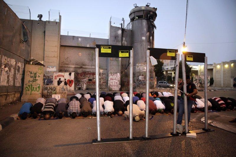 以巴問題:穆斯林在金屬探測器安檢門外進行禮拜(AP)