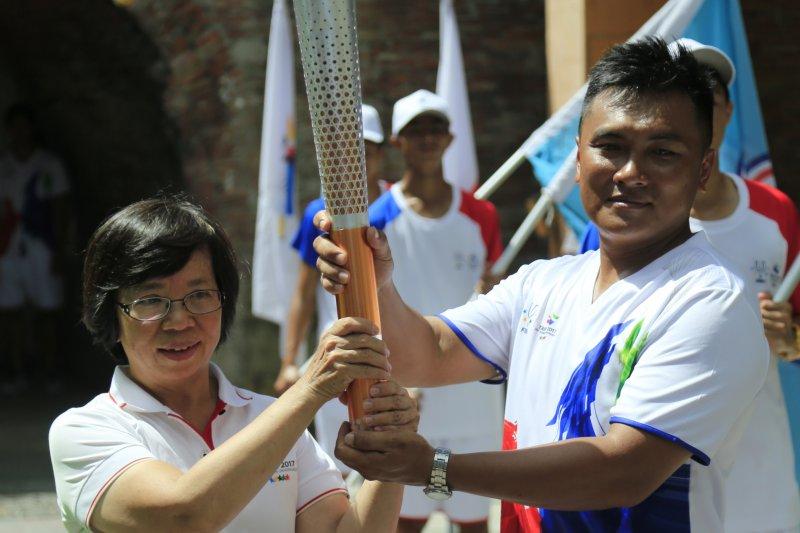 世大運執行長蘇麗瓊(左)將聖火傳遞給選手。(屏東縣政府提供)