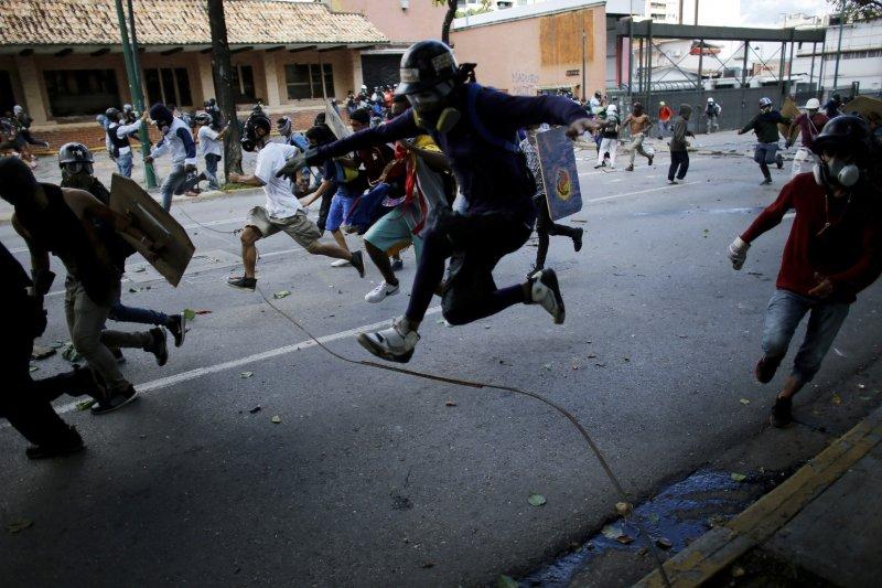 委內瑞拉26日發起全國大罷工48小時,反政府的示威者逃離進逼的武裝國民兵(AP)