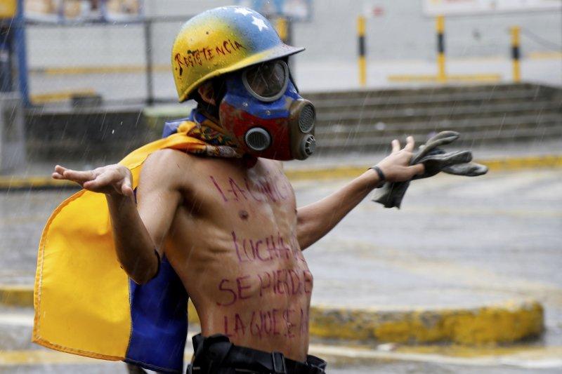 7月28日,委內瑞拉首都卡拉卡斯一名反政府示威者在雨中與國民兵對抗(AP)