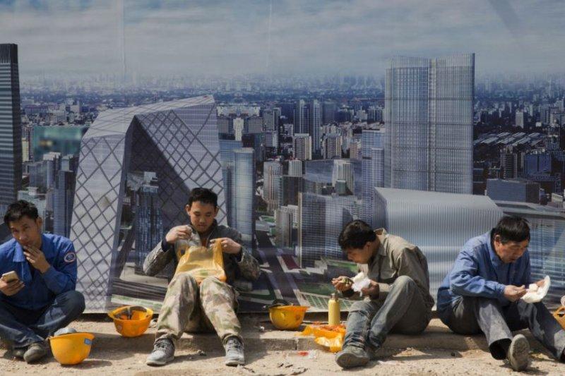北京一個建築工地外面,工人吃午飯,旁邊的板子上有中央商務區的影像(美國之音)