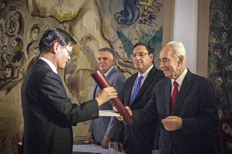 2014年沃爾夫獎的頒獎典禮上,作者從以色列總統、諾貝爾和平獎得主裴瑞斯(Shimon Peres)之手接下獎狀。沃爾夫獎肯定了作者 對於醣分子科學、醣化學合成及醣蛋白合成的開創性貢獻。(科學人提供)