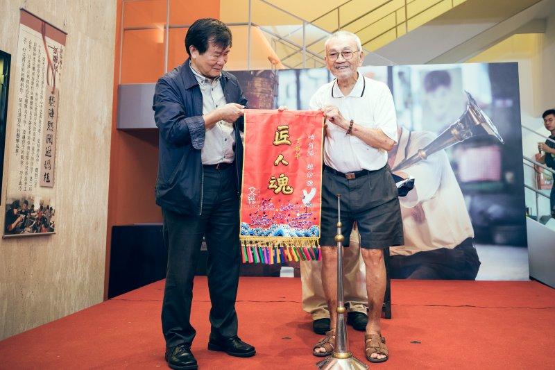 文化總會副會長江春男(左)贈送手工刺繡的匠人魂錦旗給魏幼謙。(中華文化總會提供)