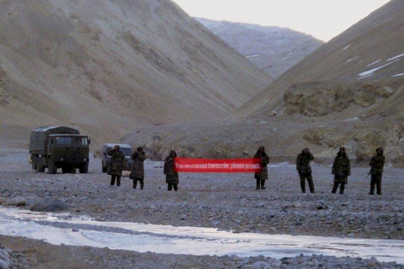中印邊界軍事對峙:中國軍隊拿著寫著「你越界」的標語布條(AP)