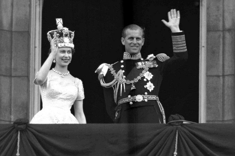 1953年女王正式登基,在白金漢宮的陽台與菲利普親王向群眾揮手。(美聯社)