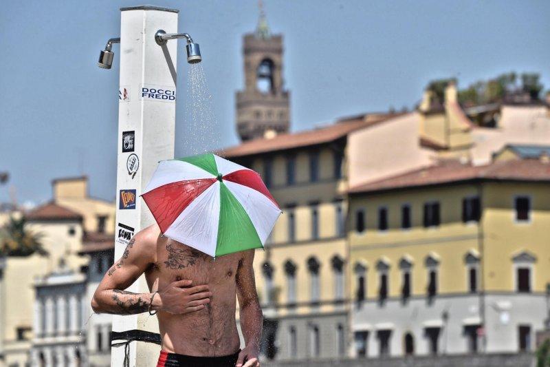 義大利近日高溫,中部古城佛羅倫斯一名男子頂著小傘,在戶外沖涼(AP)