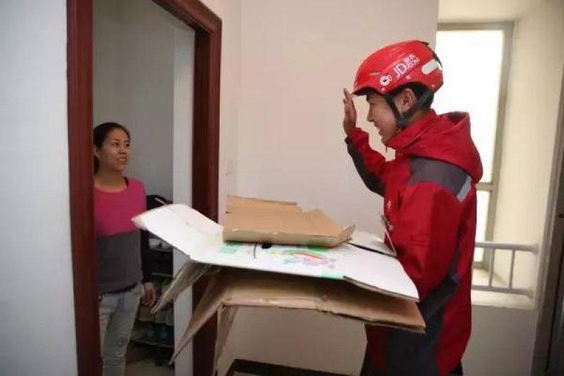 電商消費成中國全民生活的日常,導致瓦愣紙箱供不應求,連日本業者也感受到威力。圖為京東快遞員上門回收紙箱(新華社)