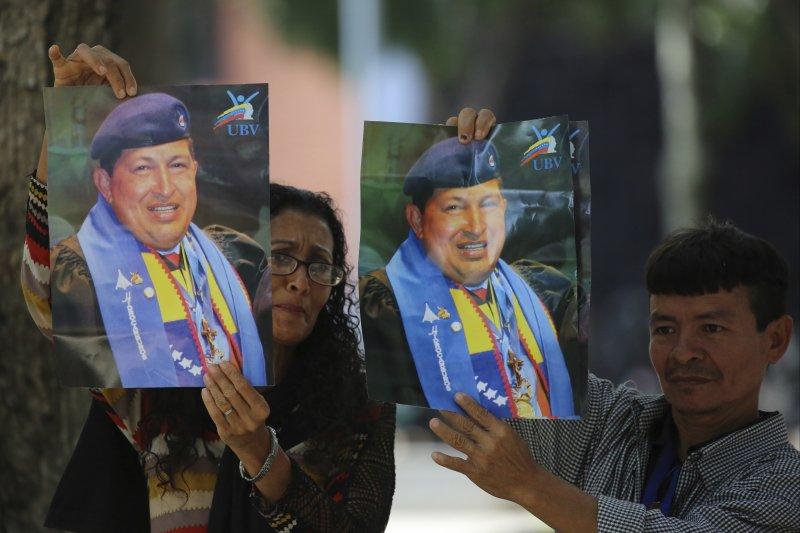 支持已故總統查維茲的民眾,上街高舉查維茲肖像力挺政府。(美聯社)