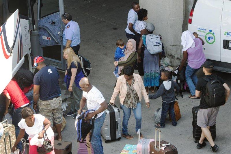 從美國偷渡至加拿大尋求庇護的難民2日提著行李來到蒙特婁的奧運場館(AP)
