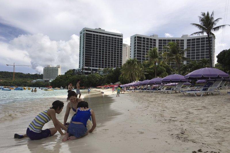 關島海灘上戲水的人們。(美聯社)