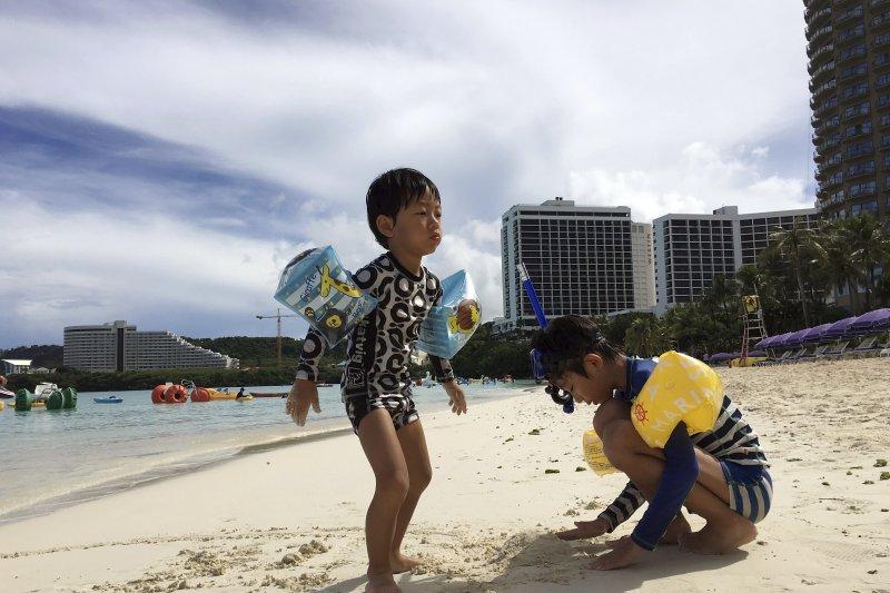 關島海灘上戲水的小朋友。(美聯社)