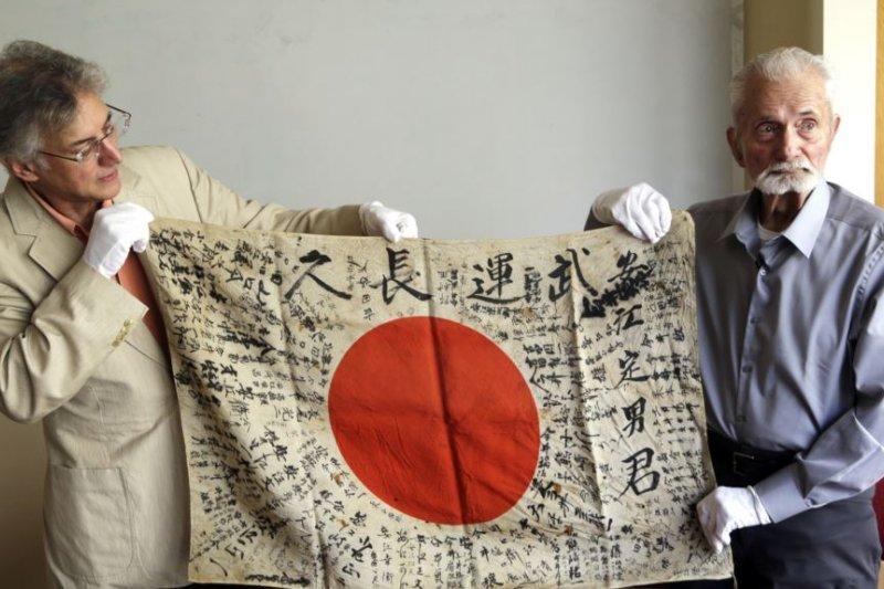 2017年8月7日,93歲的美國二戰老兵馬文・斯特羅姆伯(右)與「盂蘭盆協會」執行主任雷克斯・茲卡展示斯特羅姆伯70多年前從一名戰死日軍身上取下的「武運長久」旗。斯特羅姆伯將親自把這面旗還給死者的家人。(美國之音)