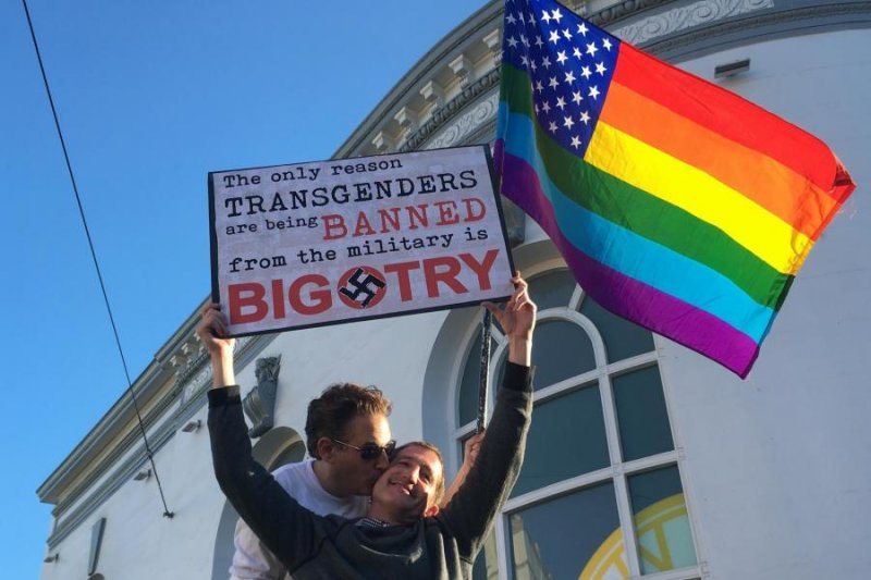 美國總統川普7月宣布禁止跨性別人士從軍後,引發外界抗議,圖為一對同志情侶手拿彩虹旗與標牌抗議川普的決定,標牌寫著:「禁止跨性別者從軍的唯一原因是偏執。」