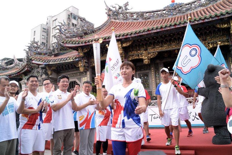 世大運聖火傳回台北,以萬華龍山寺為起點,由各界體育好手接棒繞跑台北舊城區。(台北市政府提供)