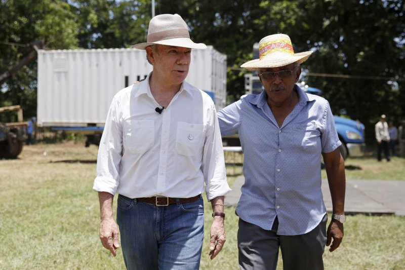 哥倫比亞總統桑托斯(左)與FARC領袖葛梅茲(Joaquin Gomez)(AP)