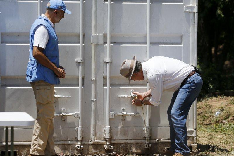 哥倫比亞總統桑托斯把最後一個裝滿步槍的貨櫃上鎖(AP)