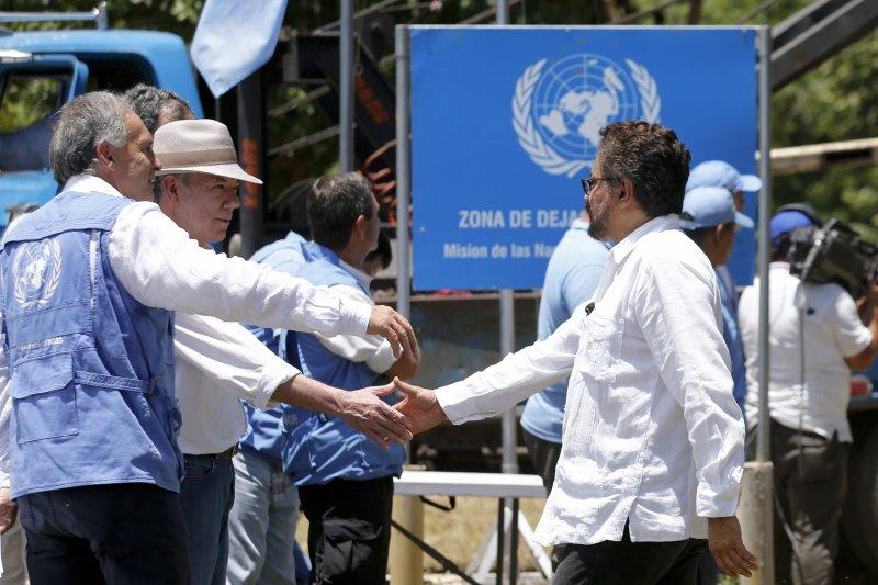 哥倫比亞總統桑托斯(戴帽者)與FARC代表馬凱茲握手(AP)